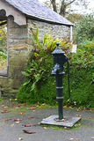 Ancient Water pump. Ancient green water pump located in Cornwall UK, but no longer in use just a decorative element stock photos