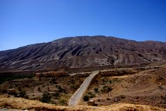 Ancient Water-Scarred Desert Mountain. Desert mountains in Oman, scared with evidence of millions of years of changing watercourses and tectonic movement royalty free stock images