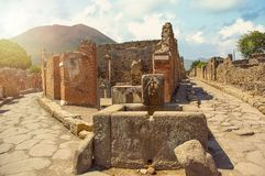 Ancient water well in Pompeii on Mount Vesuvius background, Campania, Italy. Roman streets royalty free stock photos