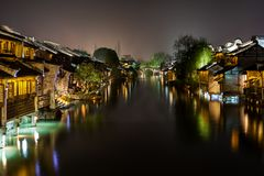 Ancient Watertown in China at night, Wuzhen near Shanghai. Bridge and houses Royalty Free Stock Photo