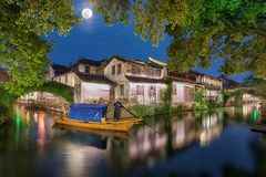 The ancient watertown Zhouzhuang in China with full moon. Gondolier crossing a canal of the ancient watertown Zhouzhuang in China, during night with full moon royalty free stock photography
