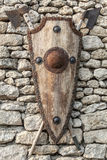 Ancient weapons on a stone wall. Wooden shield with iron accents Royalty Free Stock Image
