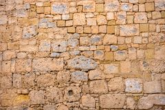 Ancient weathered wall limestone like background in Malta, close up. Ancient weathered brown wall limestone like background in Malta, close up stock image