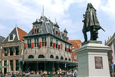 Ancient weigh house and tourists in dutch city Hoorn. Netherlands, province North-Holland, city, small town Hoorn: on the town square, street,  de Roode Steen Stock Photography