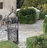 Ancient well in the cured Italian-style garden of a villa Royalty Free Stock Photo