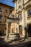 Ancient well on Piazza Grande square in Montepulciano, Tuscany. The well is decorated with sculptures of griffins and lions holding symbol of Medici family Royalty Free Stock Images