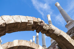 Ancient white columns and arches over blue sky. Background, fragment of ruined roman temple in Smyrna. Izmir, Turkey Stock Photos