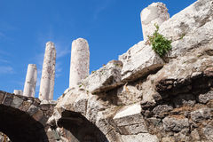 Ancient white columns and arches over blue sky. Background, fragment of ruined roman temple in Smyrna. Izmir, Turkey Stock Photo