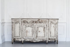 Ancient white commode bureau with paint peeled off on luxury wall design bas-relief stucco mouldings roccoco elements Stock Photo