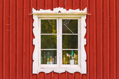 Ancient white window in a red wooden Swedish house. Ancient weathered white window in a red wooden Swedish house Royalty Free Stock Photo
