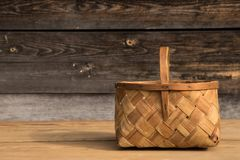 Ancient wicker basket on a wooden background. Selective focus. Free space for text. stock photo