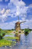 Ancient wind mill near a blue canal on a summer day at the Kinderdijk, The Netherlands stock photography