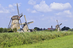 Ancient wind mills in a fresh green field on a summer day at Royalty Free Stock Image