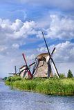 Ancient wind mills near a blue canal on a beautiful summer day at Kinderdijk, Holland stock images