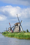 Ancient wind mills near a blue canal on a summer day, Netherlands Royalty Free Stock Photography