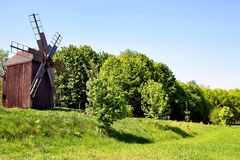 Ancient windmill on a hill in a field. Against the background of green grass. Historic site. Stock Images