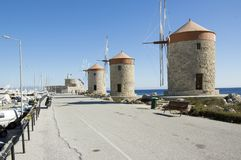 Ancient windmills on stony Rhodes coastline in harbor, old historic buildings, place of interest, blue sky. Ancient windmills on stony Rhodes coastline in harbor royalty free stock images