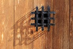Ancient window black metal jail grid wooden door Stock Images