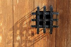 Ancient window black metal jail grid wooden door Royalty Free Stock Photos