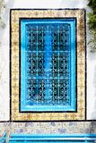 An ancient window with an ornament and a blue iron grating in Ar. Abic style against a white wall Stock Images