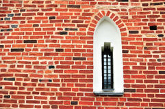 An ancient window on a red brick wall Stock Image