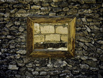 Ancient window in a stone wall with wine on the brick wall of hopelessness. Ancient window in a stone wall in the fortress with wine on the brick wall of Stock Photo
