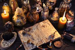 Ancient witch book with magic spell, black candles and decorated bottles royalty free stock photos