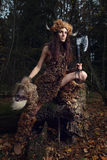 The ancient woman in the forest with an ax in his hand. Stock Photo