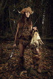 Ancient woman hunter in the forest with an ax in his hand. Histo Royalty Free Stock Photography