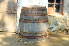 Ancient wooden barrel. An ancient wooden barrel in front of the wall stock image