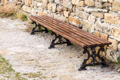 Ancient wooden bench. Near the walls of the Genoese fortress royalty free stock image