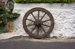 An ancient wooden broken wheel stands near the whitewashed wall with plants. Ancient wooden broken wheel stands near the whitewashed wall with plants Stock Photography