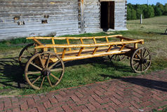 The ancient wooden cart on wooden wheels. The animal-drawn old cart costs outside near the house as an exhibit of the museum. The Royalty Free Stock Images