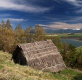 Ancient wooden Celtic house. On hillside in outdoor archaeological museum with Liptovska house in background, Havranok, Slovakia Stock Photos