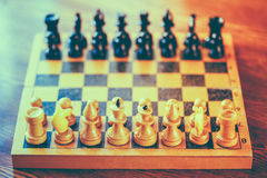 Ancient wooden chess standing on chessboard Royalty Free Stock Photos