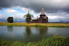 Ancient wooden church beyond the river,stormy sky stock photo