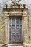Ancient wooden church door. Surrounded by weathered plaster Royalty Free Stock Photography