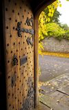 Ancient wooden door ajar showing outside wall and leaves stock photos