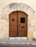 Ancient wooden door with arch in stone wall Stock Photo