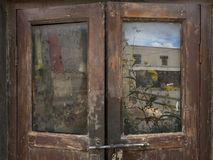 An ancient wooden door in the Buddhist monastery of Tabo, the glass reflects bright Buddhist prayer flags and yellow flowers, Hima. Ancient wooden door in the Stock Photos
