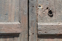 Ancient wooden door fragment. Fragment  of ancient weathered wooden door with rusty ring handle Royalty Free Stock Photography