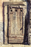 Ancient wooden door in historical house. Stone frame. Ancient worn wooden door in historical house.  An old wooden door consumed. Italian style Stock Photography