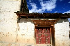 Ancient wooden door in Nepal style with yellow wall stock photo