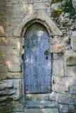 Ancient wooden door in old stone castle wall, Knaresborogh Stock Images