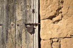 Ancient wooden door with a rusty padlock on a stone made wall Stock Images