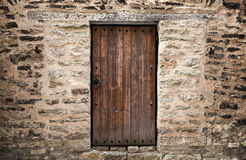 Ancient wooden door in stone castle wall Royalty Free Stock Images