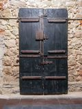 Ancient wooden door in the wall of stone stock photo