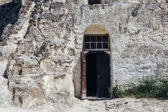 Ancient wooden door in the white chalky mountain, the entrance to the hollowed temple inside Stock Images