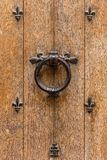 Ancient wooden entrance door with handle and fleur-de-lis ironwo. Ancient wooden entrance door with handle in the form of a ring and fleur-de-lis ironwork. The Stock Image