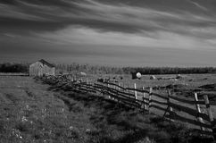 Ancient wooden fence. Ancient fence by the field. At the end of the fence is old wooden house. Far away in the horyzon is forrest Stock Image